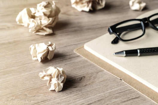Crumpled paper balls with eye glasses and notebook on wood desk with soft light