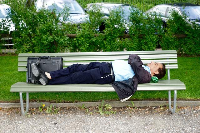 mężczyzna śpiący na ławce